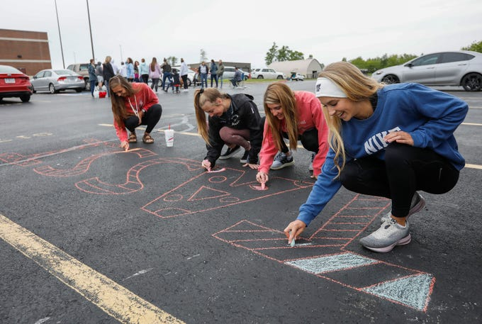 From right, Tassi Bolin, Ashton Wildermuth, Sara Morris, and Ashley Lasher, all seniors at Willard High School, decorate Tassi's parking space at the school with chalk on Monday, May 11, 2020.