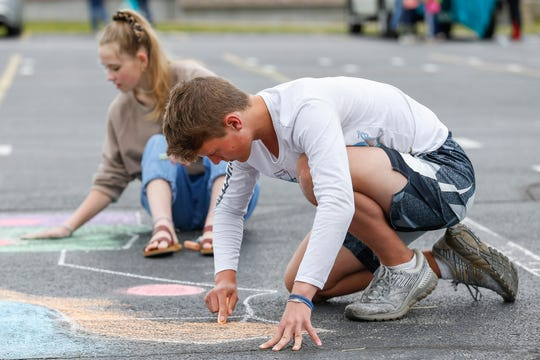 James Slyde, a student at Willard High School, decorates a parking space at the school with chalk on Monday, May 11, 2020.