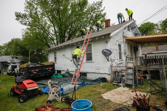 Workers with Love Or Roof remove shingles from Air Force veteran Warren Dake's roof while making improvements to his home on Monday, May 11, 2020.