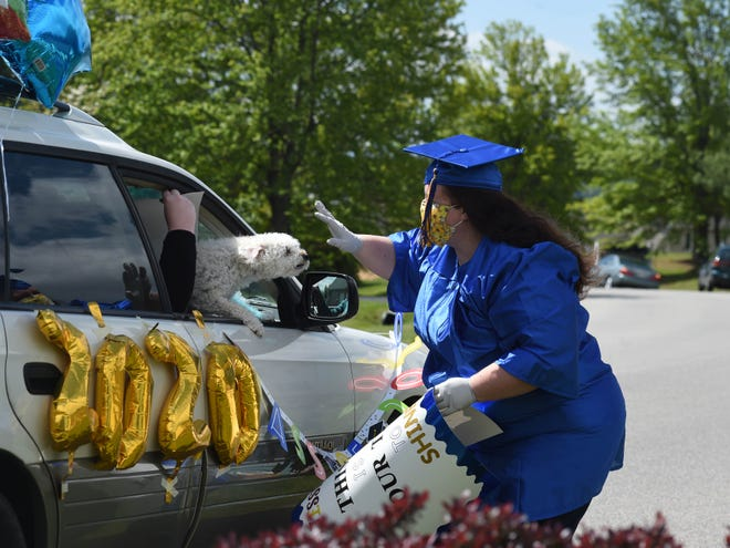 Jessica Miller waves to one of the cars in a parade that passed by her house Saturday. Family and friends were helping her celebrate graduating from Blue Ridge Community College's nursing program.