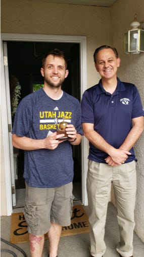 Adam DeWitt, left, receives a Golden Apple Award from the St. George Chapter of the BYU Alumni organization. DeWitt is a teacher at Pine View High School.