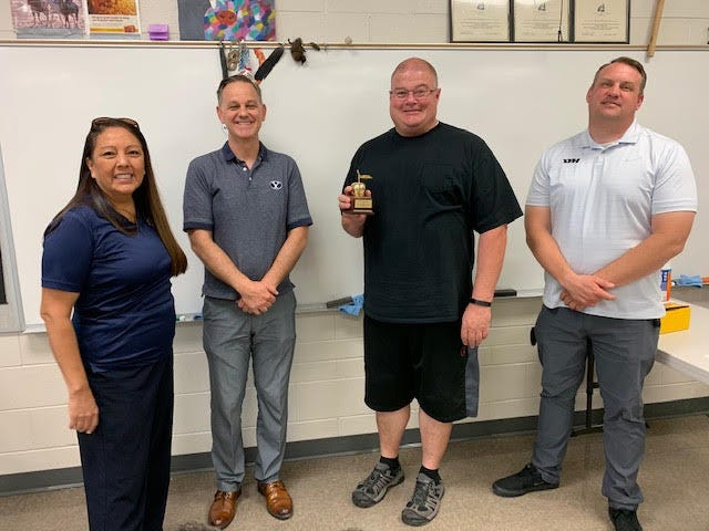 Eric Bleak, second from right, receives a Golden Apple Award from the St. George Chapter of the BYU Alumni organization. Bleak is a teacher at Desert Hills High School.