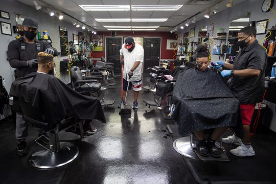 Dedrick Steward, left, Jeff Allen, middle and George Sanders IV get back to work inside Fade Barbershop on South Adams Street as barbershops and hair salons re-open their doors for the first time in weeks Monday, May 11, 2020.