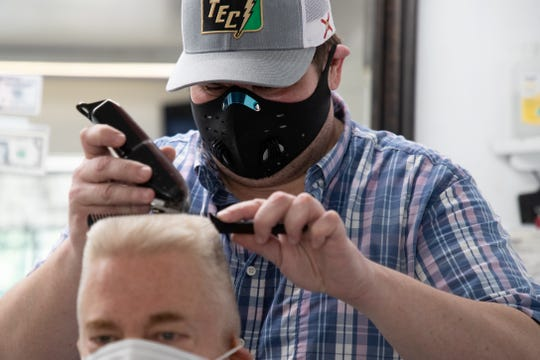 Cory Sevor, a barber at The Little Red Barber Shop on North Monroe Street, cuts a customer's hair Monday, May 11, 2020.