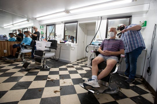 John Sites, left and Cory Sevor cut hair inside The Little Red Barber Shop on North Monroe Street as barbershops and salons re-open their doors for the first time in weeks Monday, May 11, 2020.