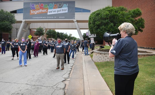 United Regional hospital CEO Phyllis Cowling speaks to doctors, nurses, staff and administrators following a group photo Monday afternoon. Cowling thanked them for their hard work during the pandemic.