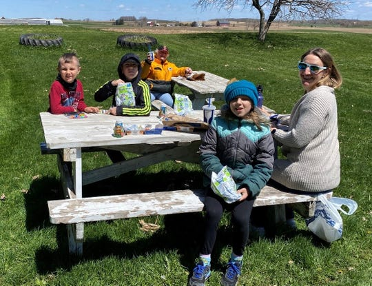 Susan sits at the second picnic table. Wyatt, Eli, Arianna, and Rachel have their lunch on the first table.