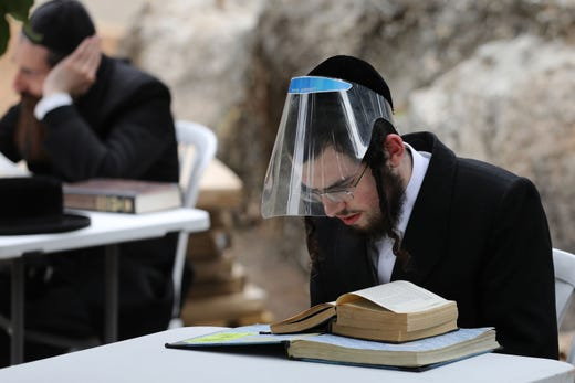 Ultra-Orthodox Jews wearing protective gear and observing social distancing amid the COVID-19 pandemic, study the Talmud and rabbinic literature at an improvised outdoors Kollel (gathering place for religious studies) at a park in their Ultra-orthodox neighborhood in Jerusalem, on May 11, 2020.