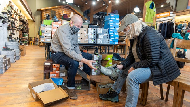 Kurt Smith wears a mask while helping a customer at the reopened Schnee's boot store on May 4, 2020 in Bozeman, Montana.