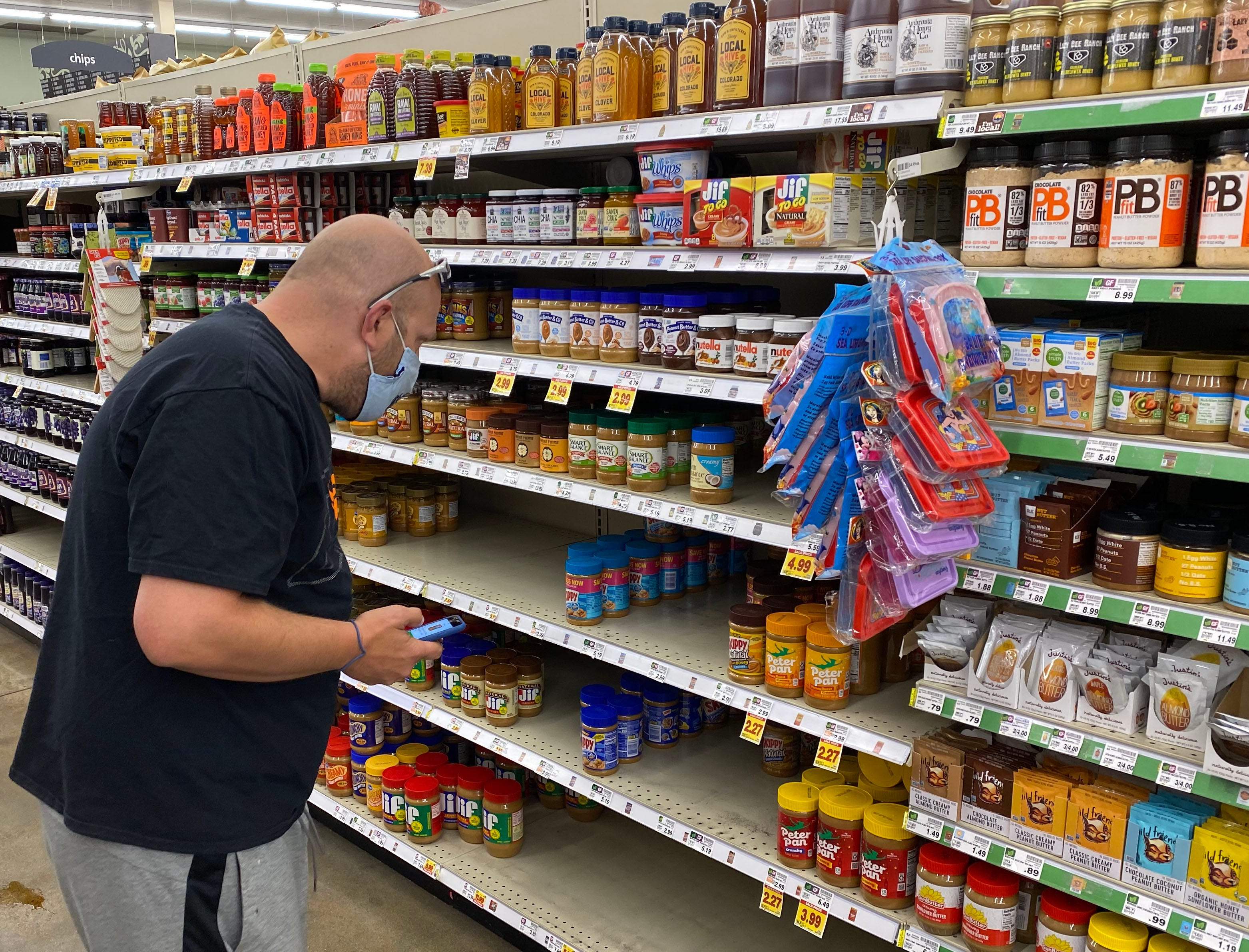 Instacart shopper Jeff Mitchell scans the shelves for the correct kind of peanut butter ordered by a customer inside a grocery store in Boulder County, Colorado.