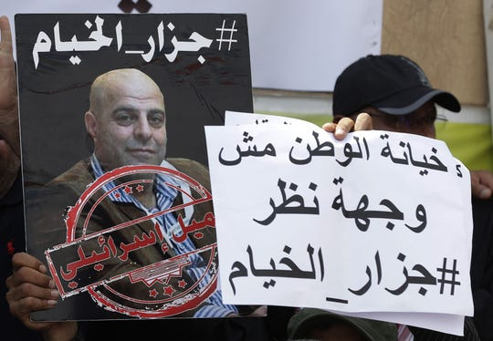 Sur cette photo du 15 septembre 2019, des membres du mouvement libanais chiite Amal tiennent une photo d'Amer Fakhoury lors d'une manifestation devant l'ancienne prison israélienne de Khiyam à la frontière avec Israël, pour exiger son procès. Ancien membre d'une milice libanaise pro-israélienne accusé par des témoins de torture, il a été libéré le 19 mars 2020 aux États-Unis, où il est un citoyen naturalisé. Le président Donald Trump a déclaré que Fakhoury, arrêté à son retour à Beyrouth en septembre, souffrait d'un cancer à un stade avancé.