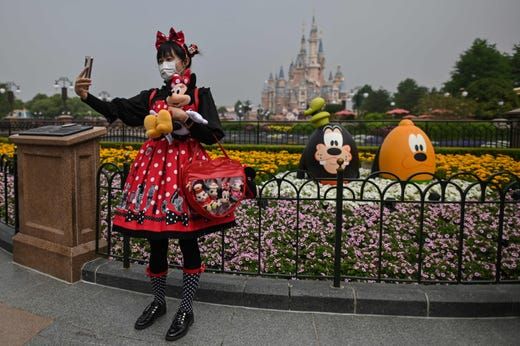 A woman wearing a face mask takes a selfie while visiting the Disneyland amusement park in Shanghai on May 11, 2020.  Disneyland Shanghai reopened on May 11 to the public after being closed since January due to the COVID-19 coronavirus outbreak.  Visits will be limited initially and must be booked in advance, and the company said it will increase cleaning and require social distancing in lines for the various attractions.