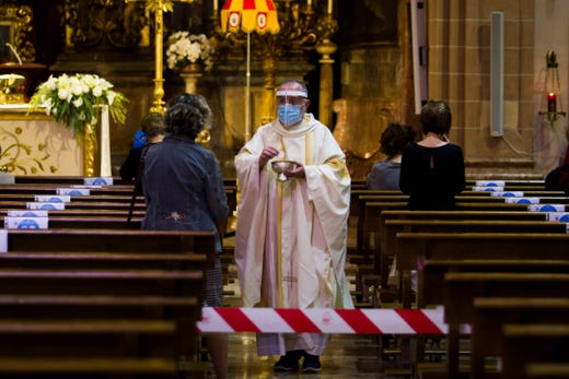 Spanish priest Antonio Gomez wearing a face mask and an acrylic shield gives the holy communion to worshippers at the San Miguel Basilica in Palma de Mallorca on May 11, 2020 as Spain moved towards easing its strict lockdown in certain regions. One of the worst-hit countries, Spain plans a phased transition through the end of June, with around half of the 47 million population being allowed out to socialize to a limited degree from Monday and restaurants offering some outdoor service.