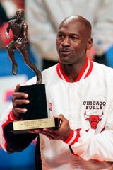 Chicago Bulls' Michael Jordan looks at the MVP award presented to him before the Bulls-Indiana Pacers playoff game in Chicago. Jordan described his final NBA championship season with the Chicago Bulls in 1998 as an electrifying year.