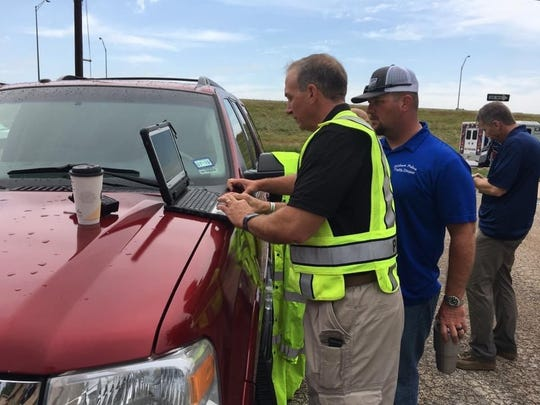 Assistant Police Chief Mike Perry reviews information regarding the tornado with Officer Tyson Kropp in a parking lot at South Danville Drive and South Seventh Street. Police Lt. Joe Tauer took this picture in the immediate aftermath of the twister that damaged multiple homes in west and north Abilene.