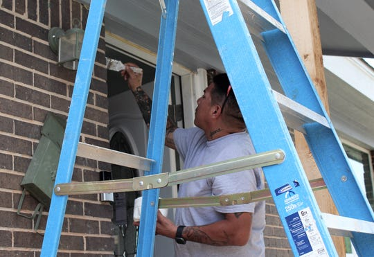 Mark Gonzales paints the door frame of the Del Rio home on Monday afternoon. The home has a new door, kitchen cabinets, paint, fixtures and appliances but is not yet ready for the family to move back.