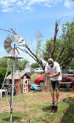 Ryan Lineweaver works his shovel into the ground at his home in the 400 block of San Jose Street, next door to battered Joe Del Rio home. Behind him is a tree struggling to survive with limbs broken by the May 18 tornado.