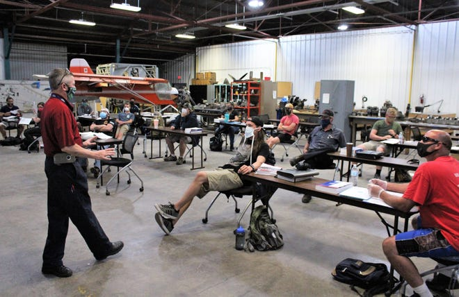 Aviation instructor Brian Wilkins and his students wear face masks and are spread apart in the hangar of the Texas State Technical College near Abilene Regional Airport. They are not meeting in classrooms to maintain social distancing.