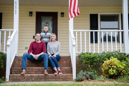"""""""This is not our forever home, but it's a greatwelcome back to Asheville home,"""" said Kathryn Bell, here on the porch of their newly purchased home with her husband, Corey, and son, Jonah, 5. """"We hope to live in it a couple of years, fix it up andsell it — and maybe make a profit off of it."""""""