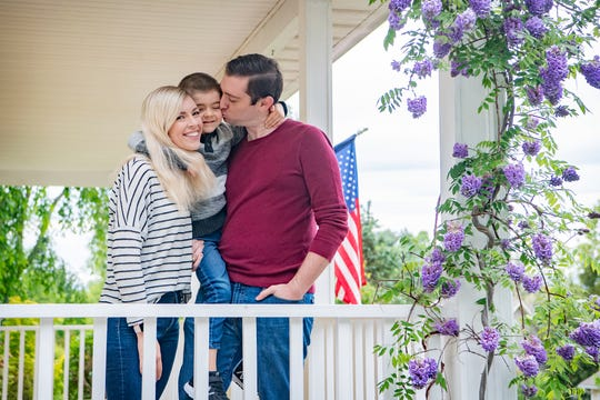 The Bell family, Corey, Kathryn and Jonah, 5, pose on the porch of their newly purchased home in South Asheville on May 8, 2020.