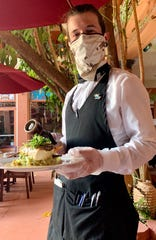 Cafe Margaux server Darrius Rodrigue delivers a seafood entree to the table wearing a mask and gloves.