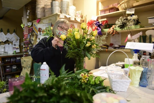 Sue Stander, owner of Norton's Flowers in Bucyrus, assembles a vased arrangement Tuesday afternoon.