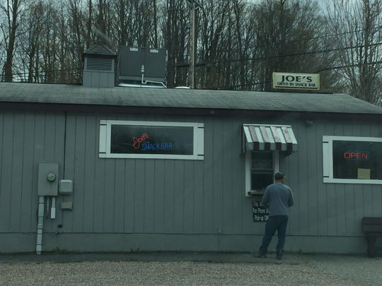 Customers at Joe's Snack Bar in Jericho wait in their cars to hear their order number called before going to the takeout window to pick up their food.