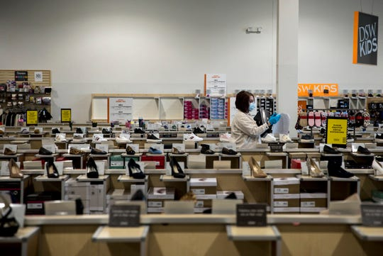 Kaylie Bryant takes inventory while working  at DSW Shoe Warehouse on Tuesday, May 12, 2020 in Springdale. Tuesday was the first day retail stores could reopen to shoppers after being closed due to the new coronavirus pandemic.