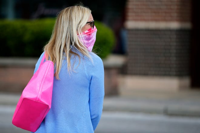 Carey Kuznar, of Montgomery, wears a mask and sunglasses as she prepares to do some shopping at the Kenwood Towne Centre in Kenwood, Ohio, on Tuesday, May 12, 2020. Kunzar said that she saw roughly a 50-50 split between people wearing masks and those without in the stores she visited, despite signage and directions to observe social distancing guidelines inside the mall.