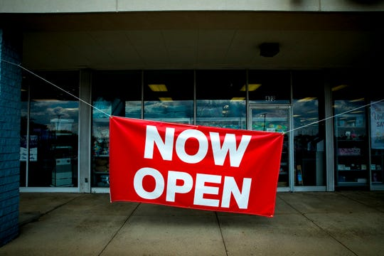 """A """"Now Open"""" sign hangs outside of retail store Tuesday Morning on Tuesday, May 12, 2020, in Springdale. Tuesday was the first day retail stores could reopen to shoppers after being closed due to the new coronavirus pandemic."""