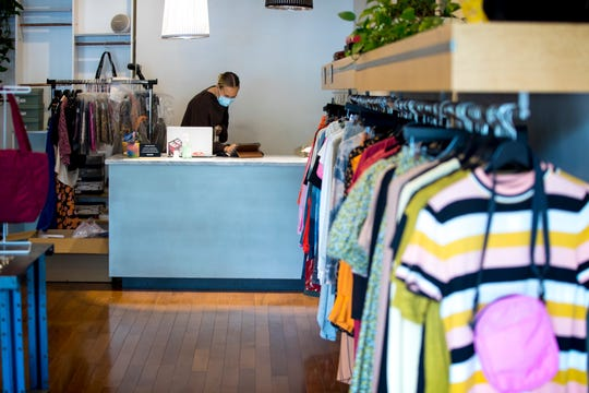 Samantha Siemer, Sloane Boutique employee, works on inventory on Tuesday, May 12, 2020, at Sloane Boutique in Over The Rhine. Sloane Boutique opened up on Tuesday  after the in person store closed in late March in response to the new coronavirus pandemic.