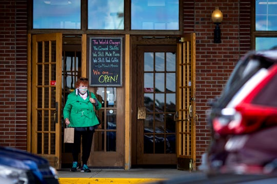 A shopper leaves Joseph-Beth Booksellers at Rookwood Commons on Tuesday, May 12, 2020. Retail opened in Ohio today after being closed since late March in response to the new coronavirus pandemic.