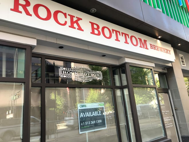 A leasing company sign and paper cover the windows Tuesday at Fountain Square fixture Rock Bottom Brewery on Sixth Street in Cincinnati.