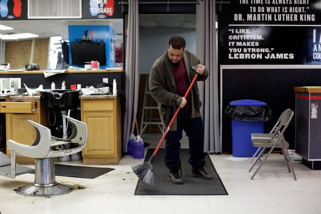 Owner and barber Tommy Mays sweeps up as he prepares for this week's reopening at Precision Blendz Barbershop in Mount Healthy May 12. Mays says the forced shutdown is the longest he's been away from work in more than two decades of cutting hair