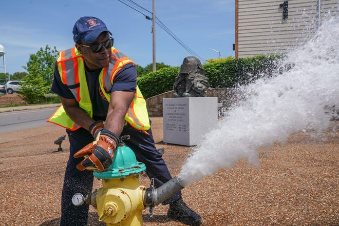 A Clarksville Fire Rescue firefighter flushes a fire hydrant near Fire Station 1.