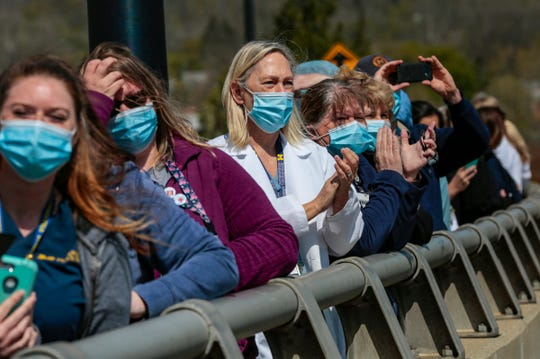 Health care workers watch as the Blue Angels fly over Ann Arbor outside of the University of Michigan Hospital on Tuesday, May 12, 2020.