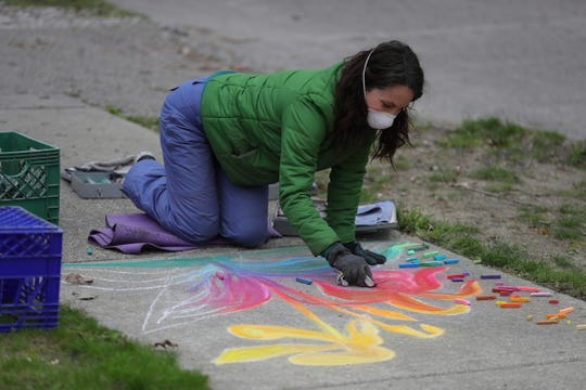 Tiffany Pugmire creates chalk art outside of her home in Oak Park Friday, May 8, 2020.