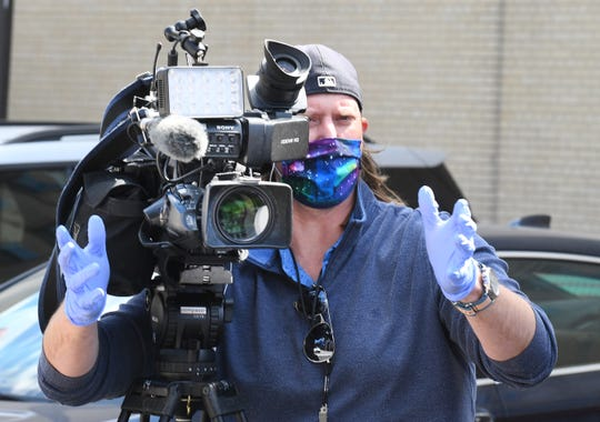 WDIV-TV news videographer Alex Atwell, wearing mask and gloves,  works with general assignment reporter Larry Spruill in the parking lot at Channel 4.