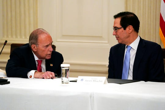 In this May 8, 2020, file photo Treasury Secretary Steven Mnuchin, right, talks with White House chief economic adviser Larry Kudlow prior to a meeting between President Donald Trump and Republican lawmakers in the State Dining Room of the White House in Washington.