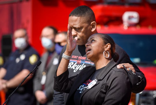 LaVondria Herbert, right, points to the sky as she and says her daughter Skylar is watching down over them, as she and her husband Ebbie Herbert, left, speak after the announcement that 10,000 PPE gowns will  be donated to the Detroit Police, Fire, and EMS departments during a press conference at the Detroit Public Safety Headquarters, Tuesday, May 12, 2020. The donation is in honor of the Herbert's 5-year old daughter Skylar Herbert, who died from COVID-19.