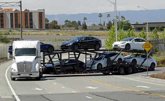 A truck hauling new Tesla vehicles leaves the Tesla factory plant on Monday, May 11, 2020, in Fremont, Calif.