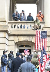 Protesters wait in line to enter the Capitol after a rally on the front steps and lawn in Lansing on April 30.