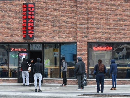 People stand a safe distance apart while waiting to pick up their orders at Bucharest Grill on Livernois Avenue in Detroit on April 23, 2020.
