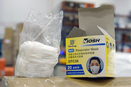 An opened box of protective masks sits on a pallet at Direct Relief's distribution center in Santa Barbara, Calif., on Wednesday, April 1, 2020.  An Associated Press investigation has found millions of medical masks, gloves, gowns and other supplies being used in hospitals across the country are counterfeits, putting lives at risk.