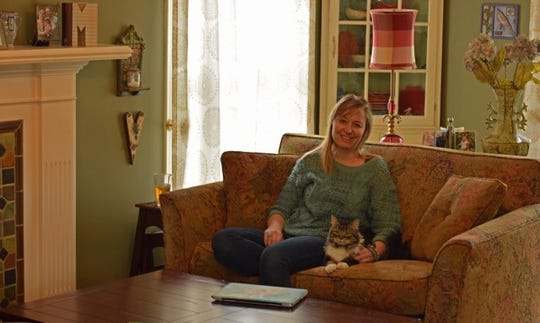 April McCrumb's favorite spot -- near the fireplace in her living room with her cat.