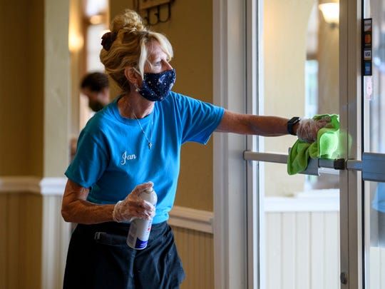 Server Jan Embry thoroughly cleans the front doors as she waits for more customers to arrive for lunch at Friendship Diner in Evansville, Ind., Tuesday afternoon, May 12, 2020. The restaurant reopened for dine-in customers on Monday and plan to be open from 6 a.m. to 3 p.m. every day.