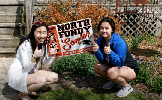Horace Mann High School seniors Mai Vang and Gabby Ciepluch pose next to a lawn sign handed out to members of the graduating class of 2020. School Districts are finding alternatives ways to help seniors celebrate graduation during the coronavirus pandemic.