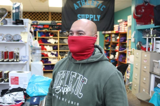 Juan Vela, owner of Fremont Athletic Supply, shows off one of the customized masks he's been selling during the coronavirus pandemic. Vela was one of several retail business owners in Fremont to reopen their doors Tuesday.