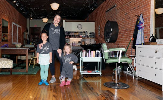 Caroline Quinn stands with her daughters, Carmen, 7, and Margo, 3, inside her Mint Salon on Main Street in Green Bay on May 12. The business is temporarily closed due to Wisconsin's safer-at-home order.