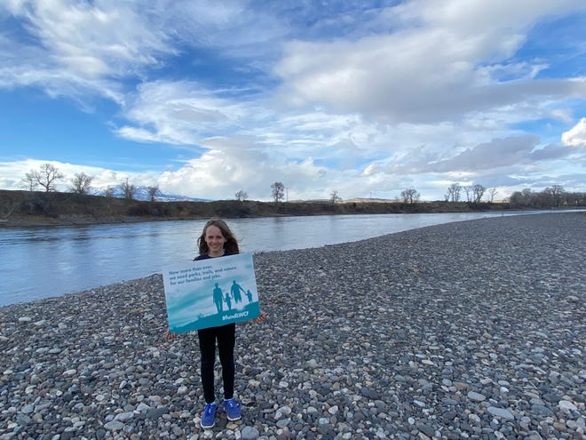 Kaia Edwards holds a placard promoting the Land and Water Conservation Fund along the shores of Montana's Yellowstone River